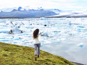 woman standing in front of glaciers showing off what to wear in iceland in winter