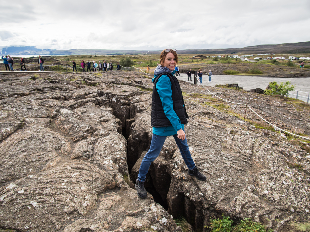 A woman standing across an opening in the a rock formation that is actually where two continental tectonic plates meet. She is wearing jeans, a blue shirt, and a black vest. One of the coolest things to do in Thingvellir National Park.