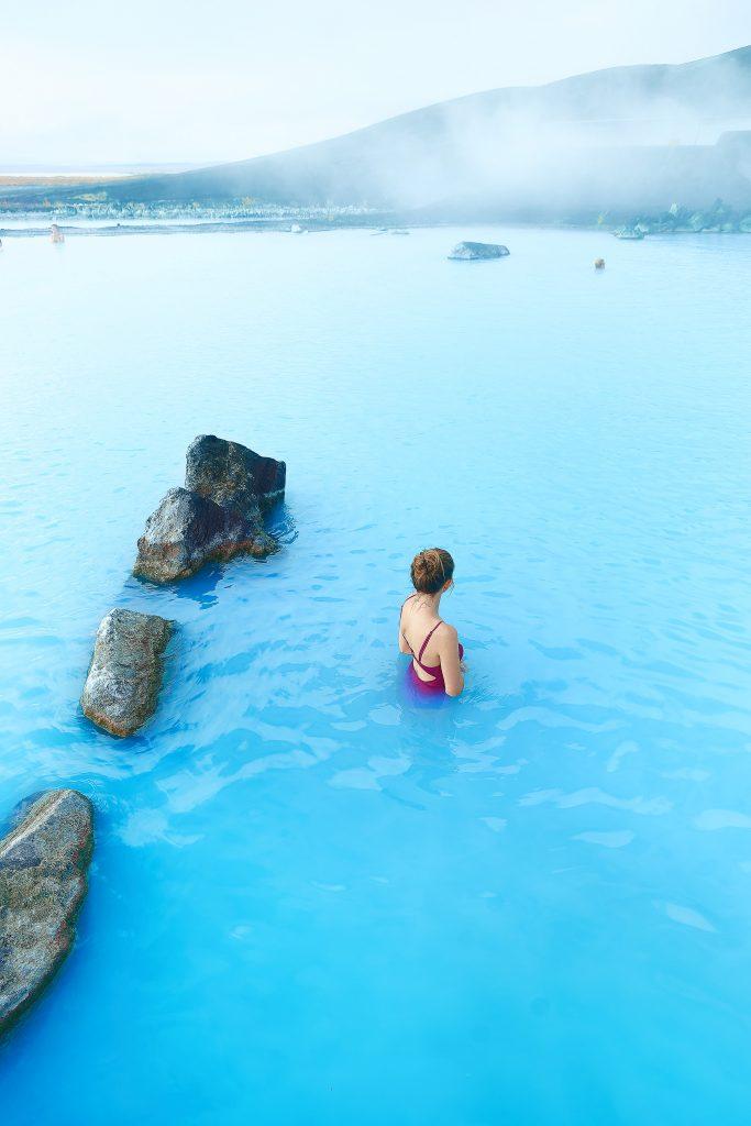 Women in pink swimsuit soaks in hot springs overlooking the Icelandic landscape.