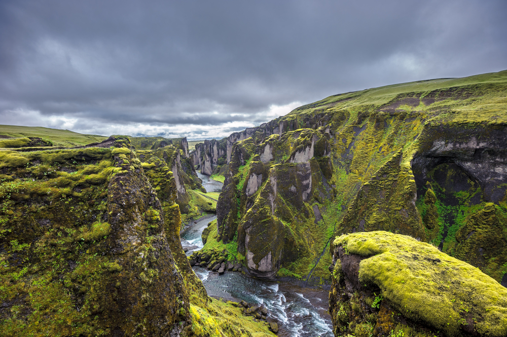 Iceland-Canyon Fjadrargljufur Canyon with mossy hills and river running through bottom