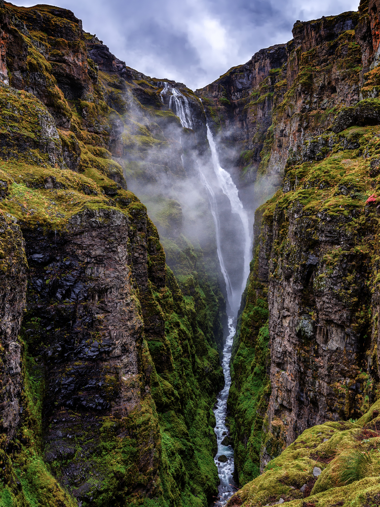 Deep Iceland Canyon Glymur Canyon with waterfall falling from high above into river below