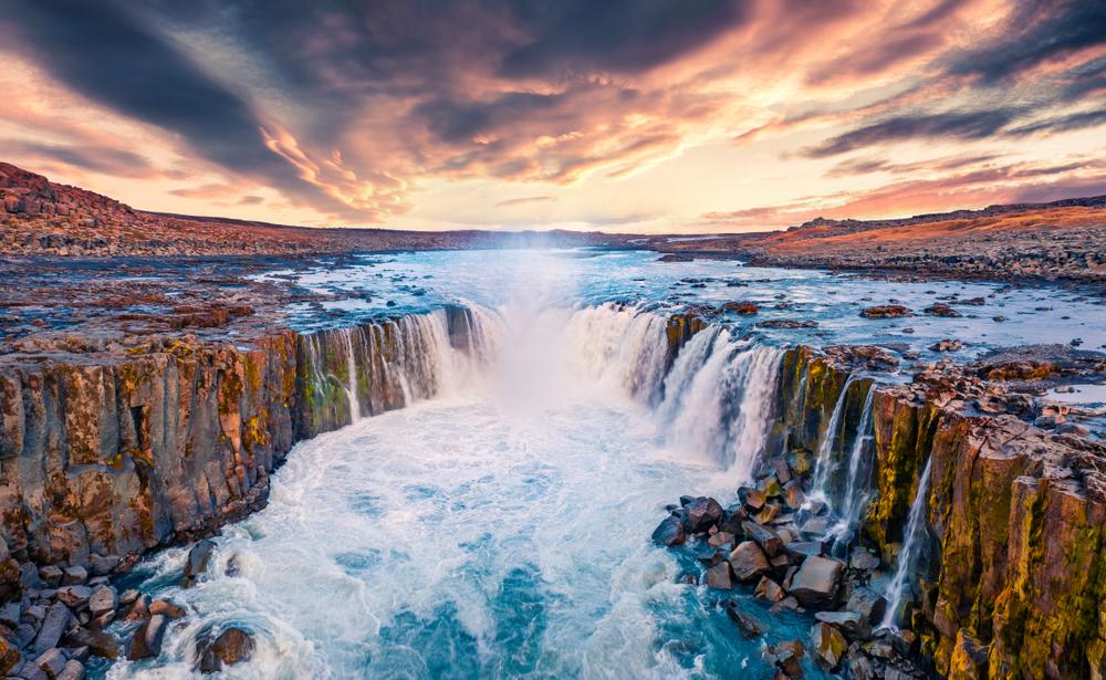 Selfoss Waterfall in Jokulsargljufur Canyon with multiple waterfalls flowing into river below at sunset