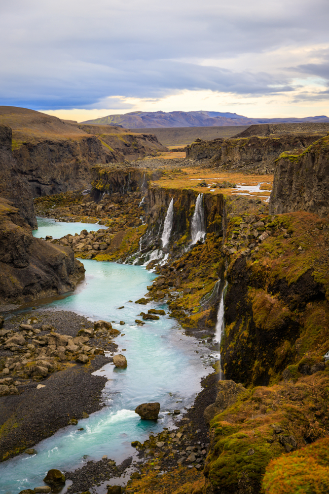 Iceland Canyon Sigoldugljufur Canyon with multiple waterfalls flowing into a glacial river
