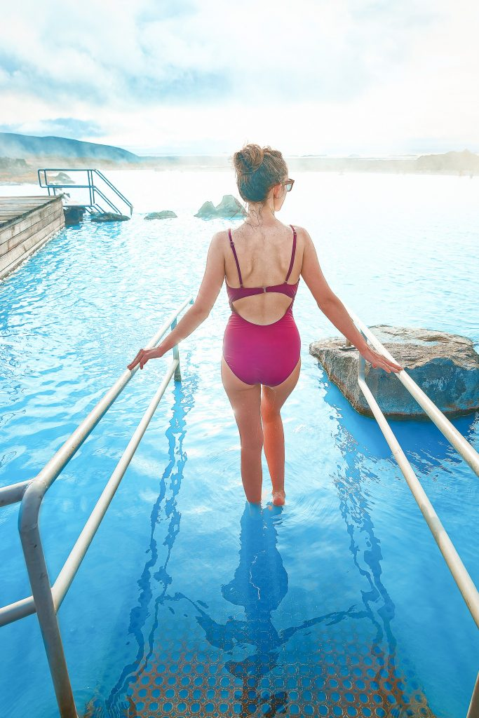 Woman in pink swimsuit walking in the blue waters of Myvatn Nature Baths.