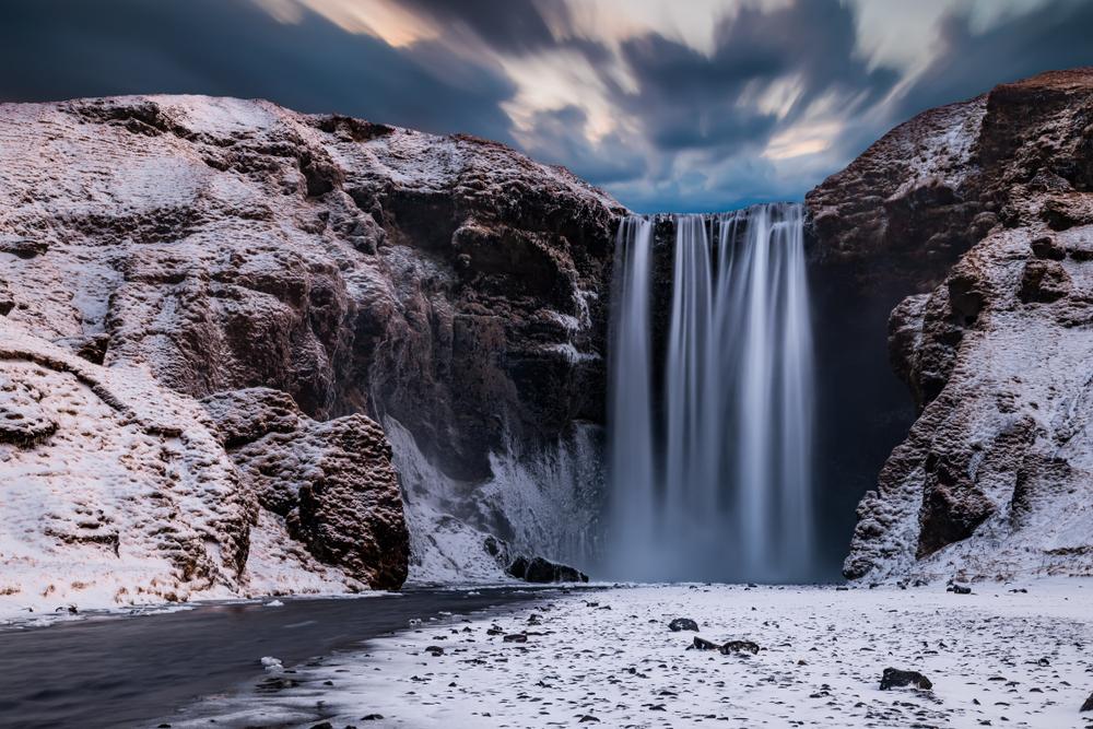 Skogafoss Waterfall flowing down in between snowy cliffs.