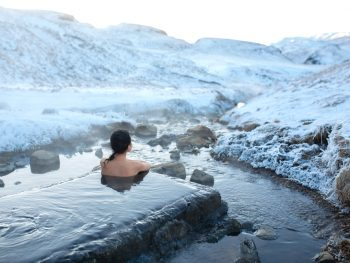 person relaxing in hot spring in iceland during winter
