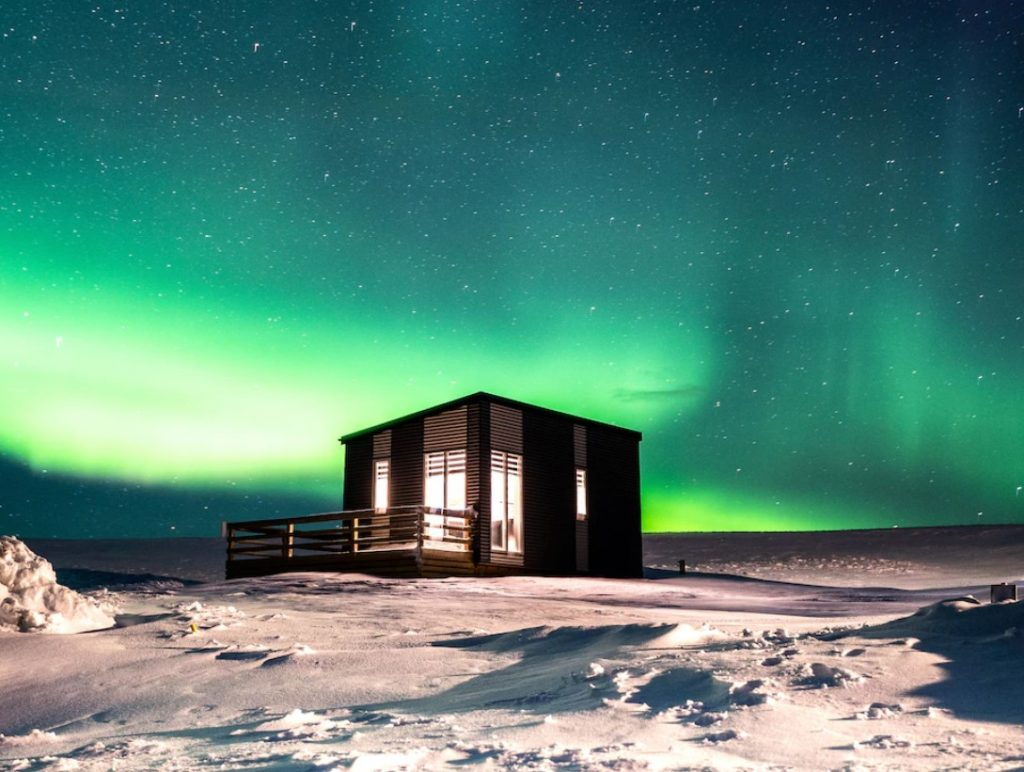 A black cottage lit up from the inside with long narrow windows on the front. It is sitting in a field full of snow and behind it you can see the Northern Lights. One of the best vacation rentals in Iceland.