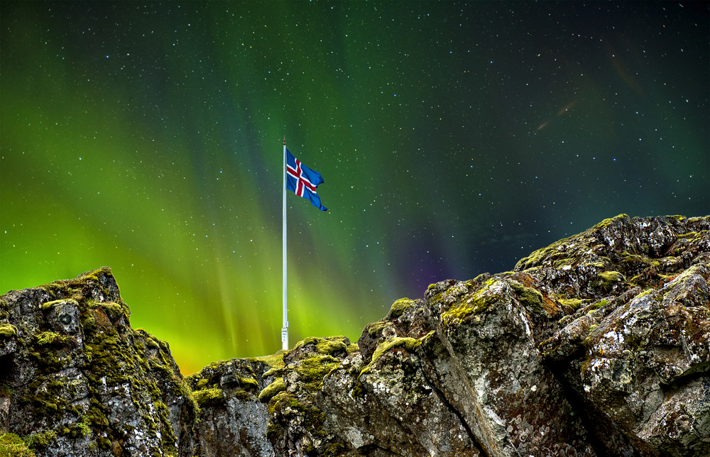 The Icelandic flag sticking out of a large rock formation. It is night time and in the sky you can see the aurora borealis.