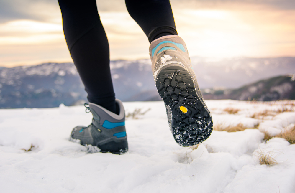 close up of a woman's hiking boots in iceland walking in snow