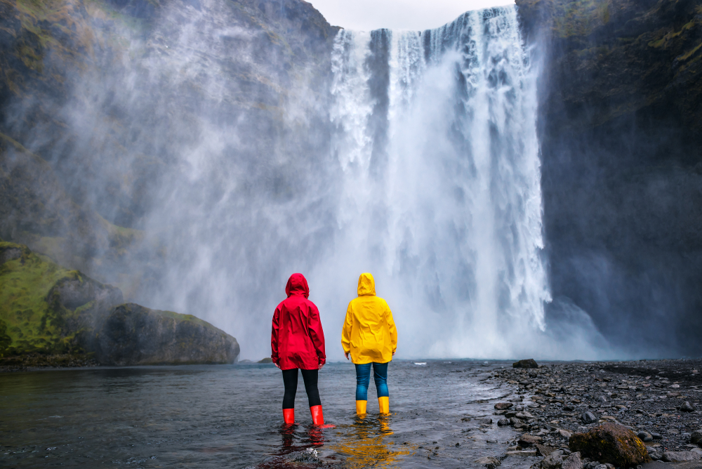 two peolple waring a yellow and red rain jacket and matching boots standing in the water looking at a waterfall