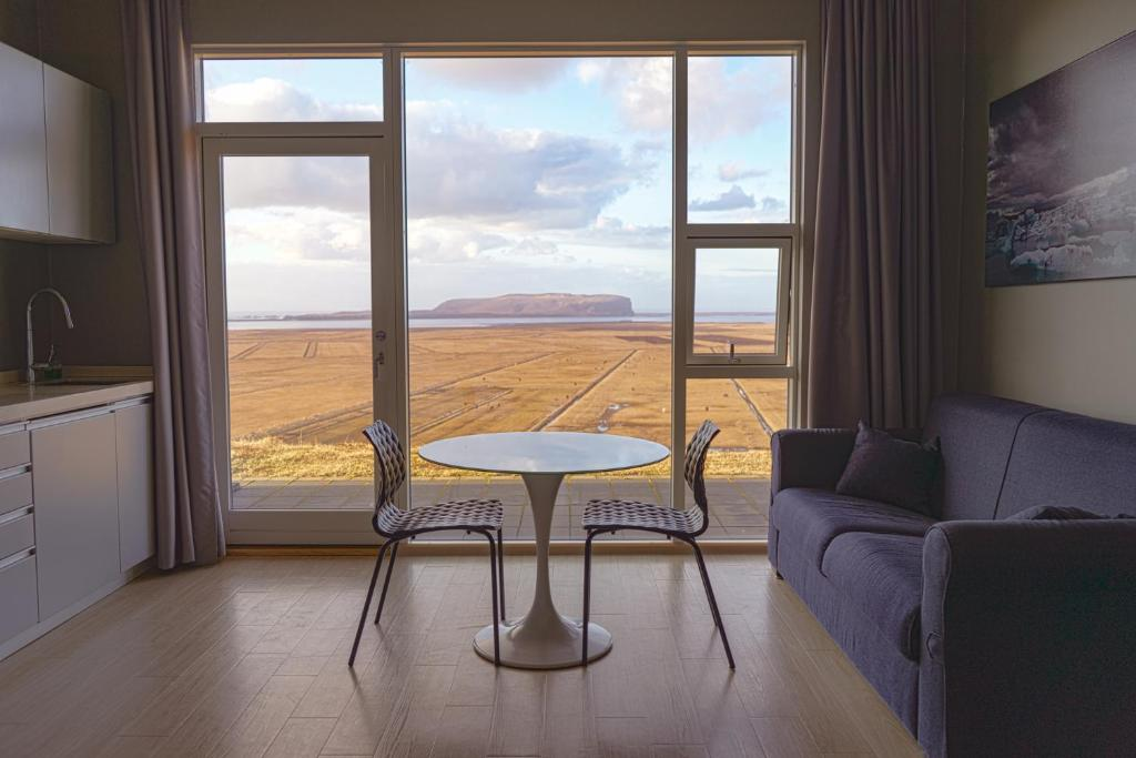 The view from floor to ceiling windows in a cottage in Vik Iceland. In the room you can see part of a kitchen counter, a couch, and directly in front of the windows is a small table with two chairs. Out the windows you can see a straw-colored field that goes on for miles before hitting the ocean. There is a large hill or mountain in the ocean water. One of the best vacation rentals in Iceland.