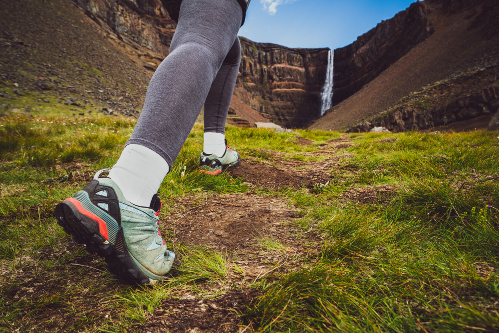 woman wearing a pair of the best boots for iceland walking up to a waterfall on a summer day