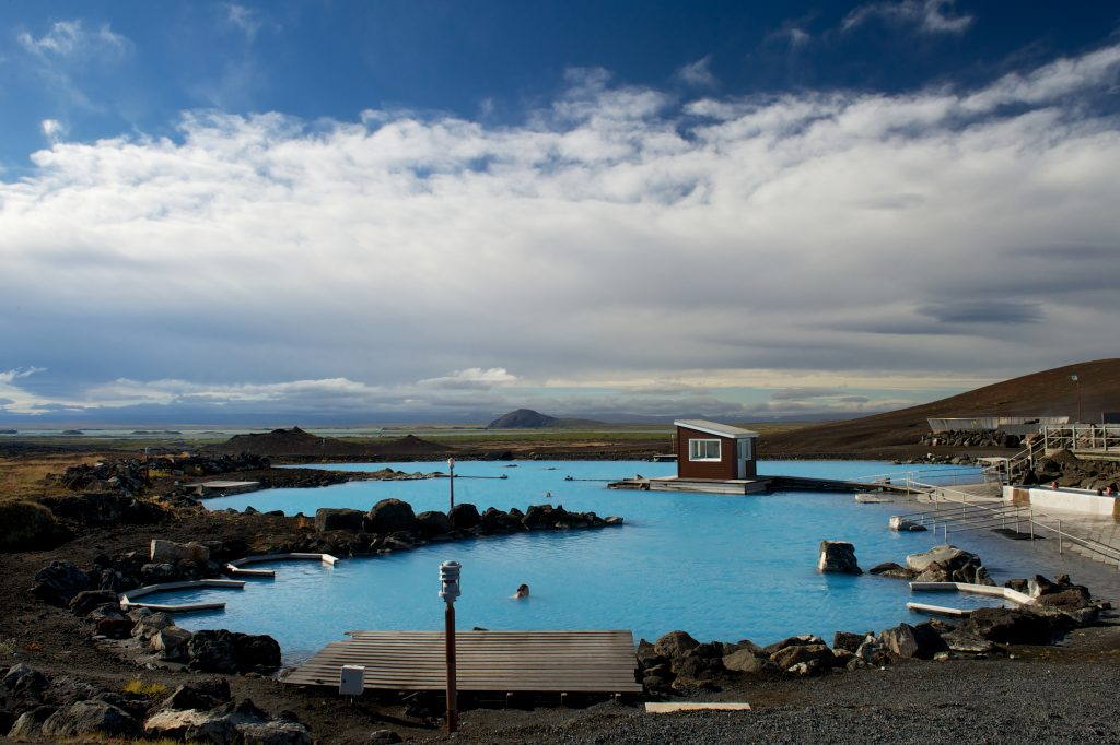 The blue waters of the hot springs shines brightly against the muted landscape in Iceland.