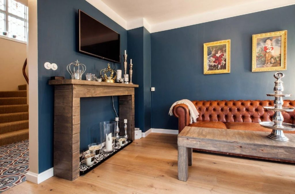 The cozy living room of one of the best vacation rentals in Iceland in central Reykjavik. The room has dark blue walls,  with paintings in ornate gold frames, a brown leather sofa, a mantel filled with candles, a wood coffee table and a tv.