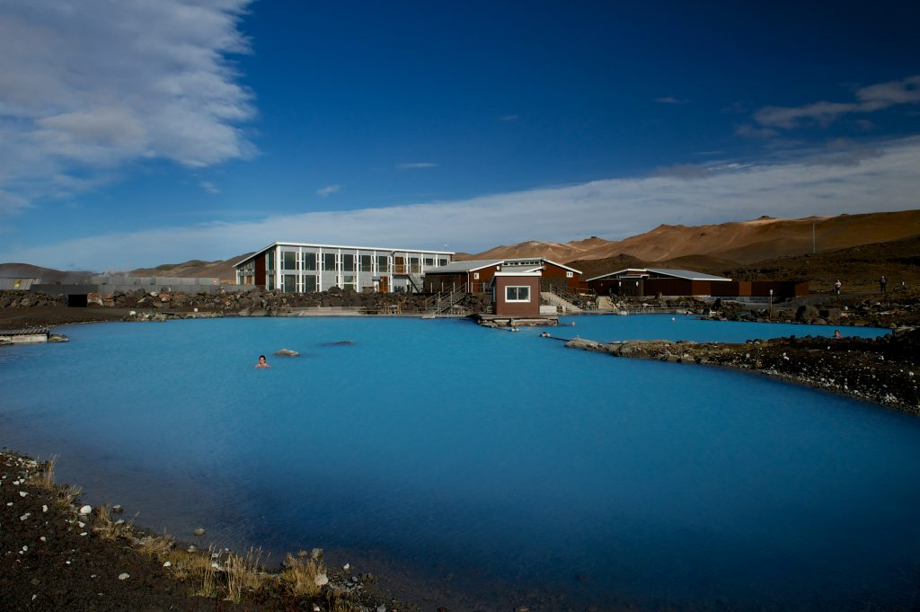 Blue skies and mountains over the facilities of the Myvatn Nature Baths in Iceland.