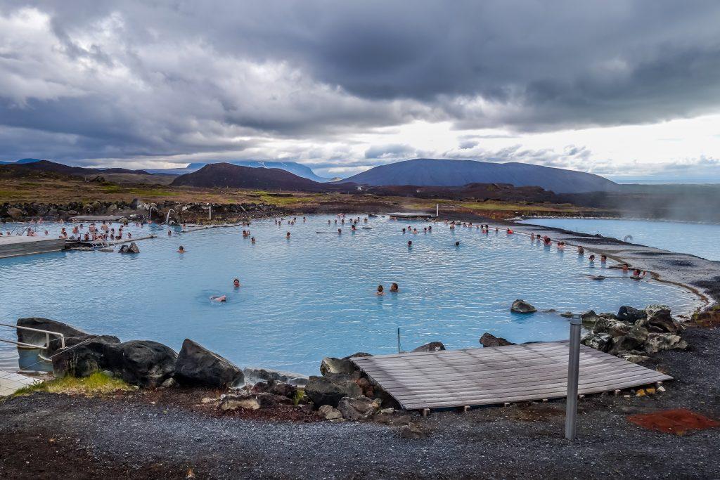 Families enjoying blue hot springs water under grey skies in Iceland.