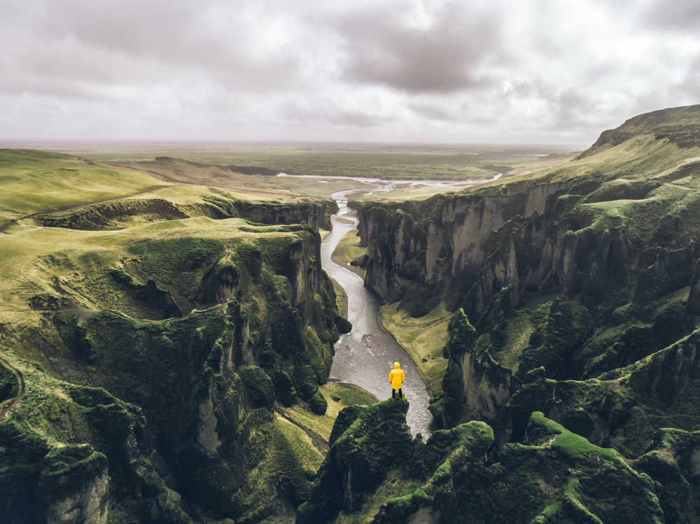 person in yellow jacket standing in one of the best canyons in iceland