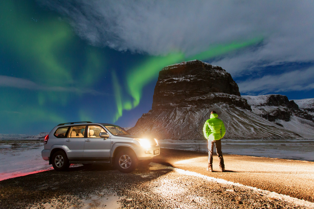 car lights lighting up a person who is watching the Northern Lights dance over some snow covered mountains