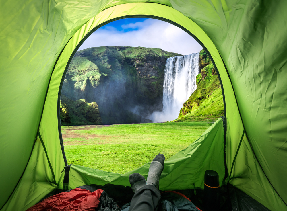 a camper at a designated campsite looking out the front of their tent at the Skogafoss waterfall