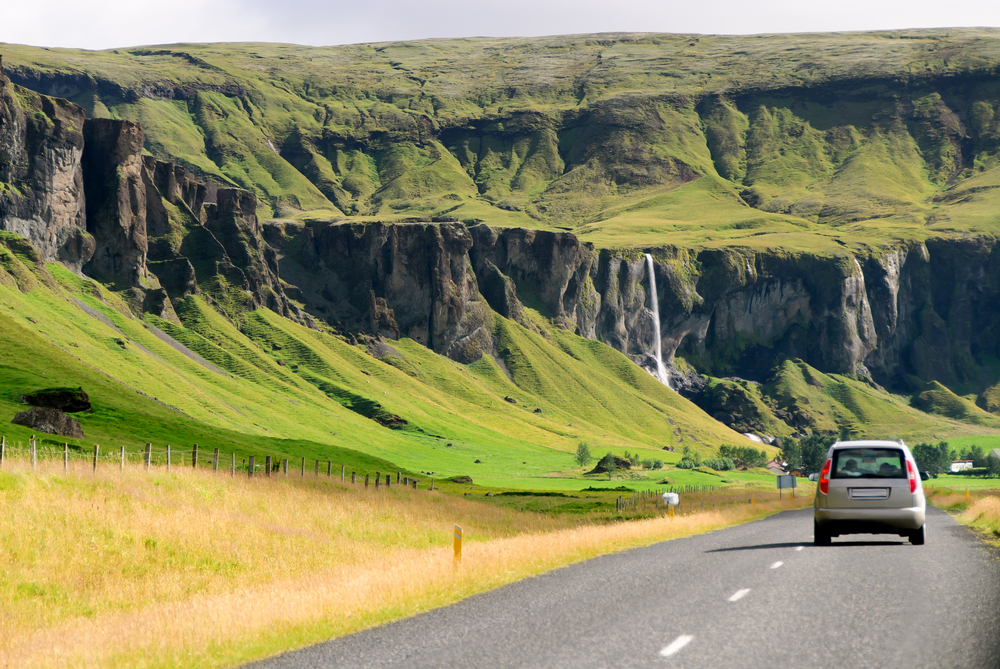 a car driving along a narrow road in Iceland towards a waterfall