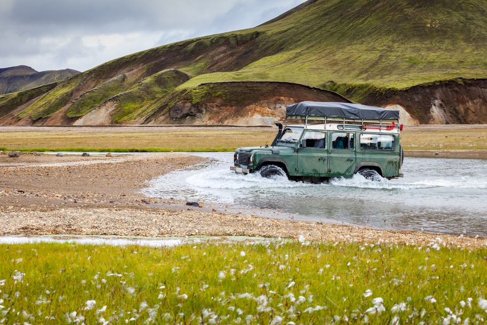 a 4WD car driving through the river in the highlands of Iceland