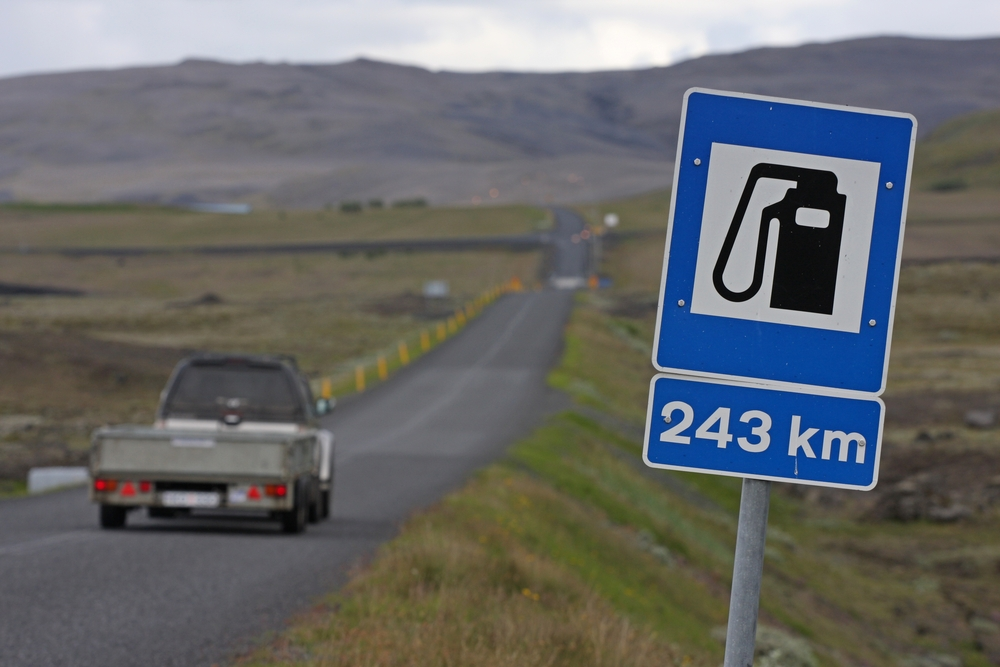 a sign on the road in Iceland indicating that the next gas station is 243 km away