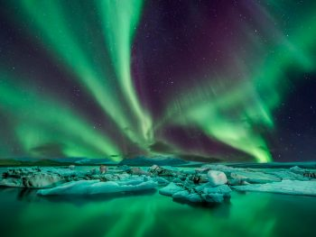 northern lights over lagoon in iceland