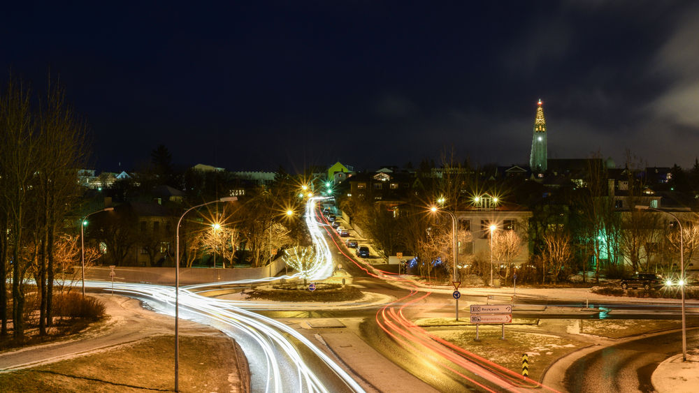 a roundabout in Reykjavik, Iceland at night time with white and red streaks indicating the cars driving through