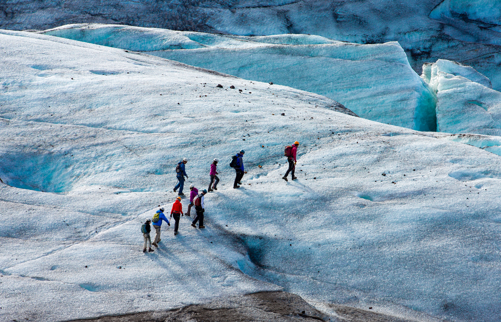 tourists trekking across a glacier in Iceland
