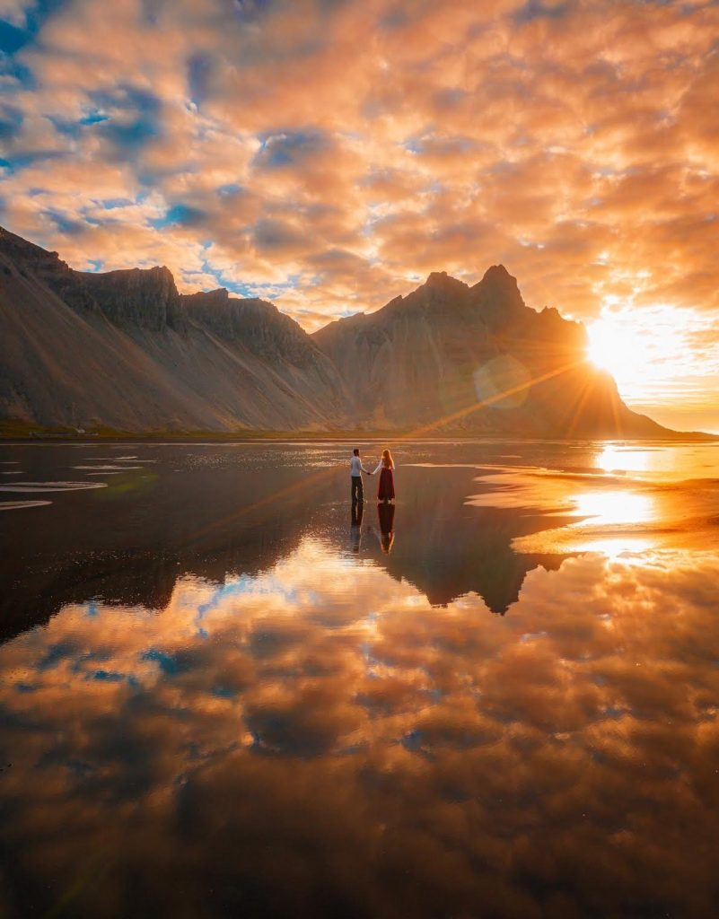 holding hands while standing in the water at Vestrahorn with the mountains in the background and the sun glowing from behind the mountains