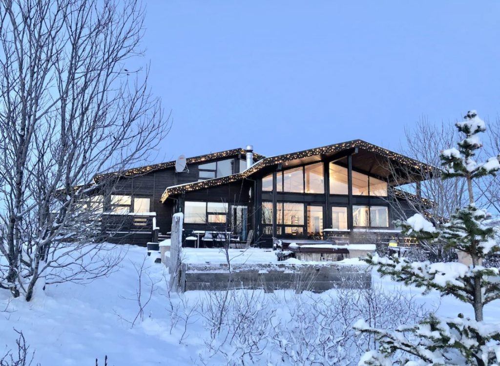 The exterior of a black luxury villa in Iceland. It has large windows, twinkle lights on the edge of the roof, and a large patio out front. The entire villa and landscape is covered in deep snow.