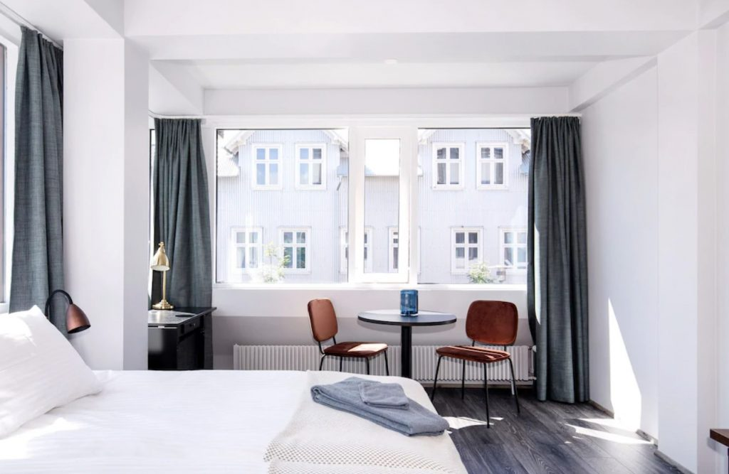 A modern bedroom in a studio apartment. The walls are white and there are large windows that have grey curtains on the sides of them. You can see white buildings outside of the windows. The room has a white bed with a copper lamp next to it, a small table with two wooden chairs, and a desk with a gold lamp. One of the best vacation rentals in Iceland.