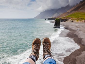 feet wearing the best boots for iceland over a black sand beach with moody clouds