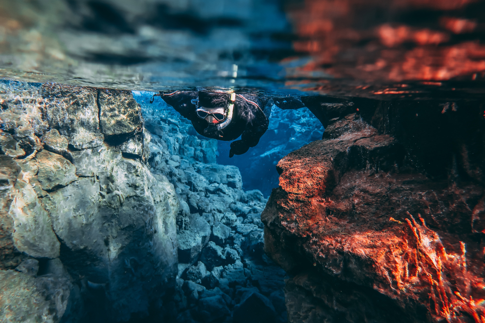 A person in scuba gear snorkeling in the Silfra Fissure. The water is crystal clear and you can see rock formations that appear gray, red, and blue.