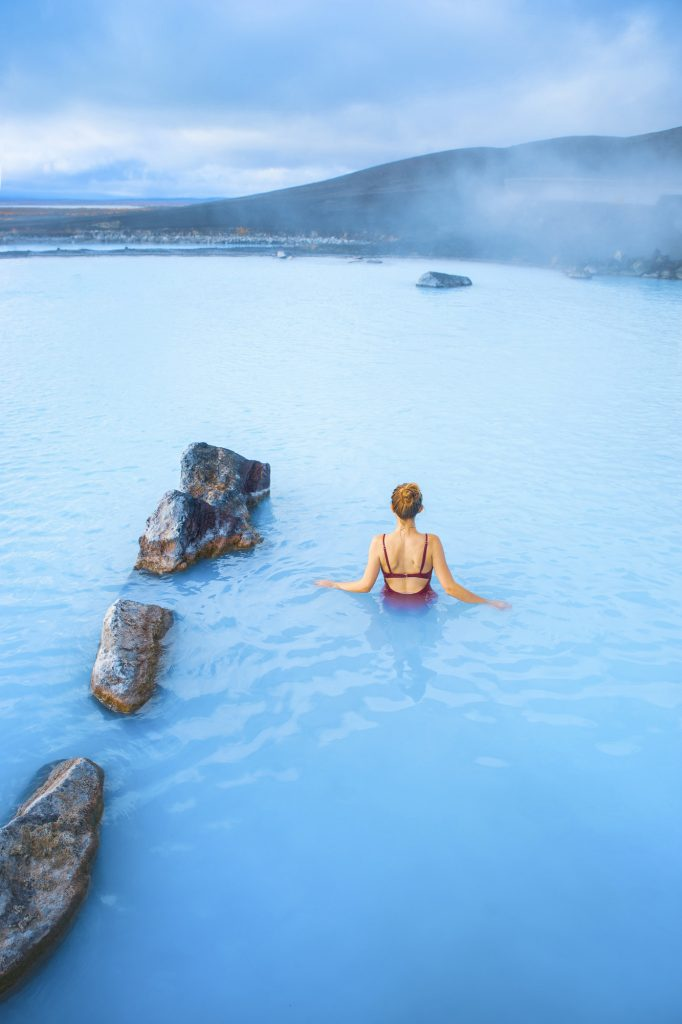 Woman in pink swimsuit enjoying the bright blue water of the Myvatn Nature Baths