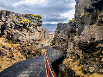 Looking down a black path between two tectonic plates that are sticking up from the Earth's crust. The trail has red guard rails and in the distance you can see people on it. One of the best things to do in Thingvellir National Park.