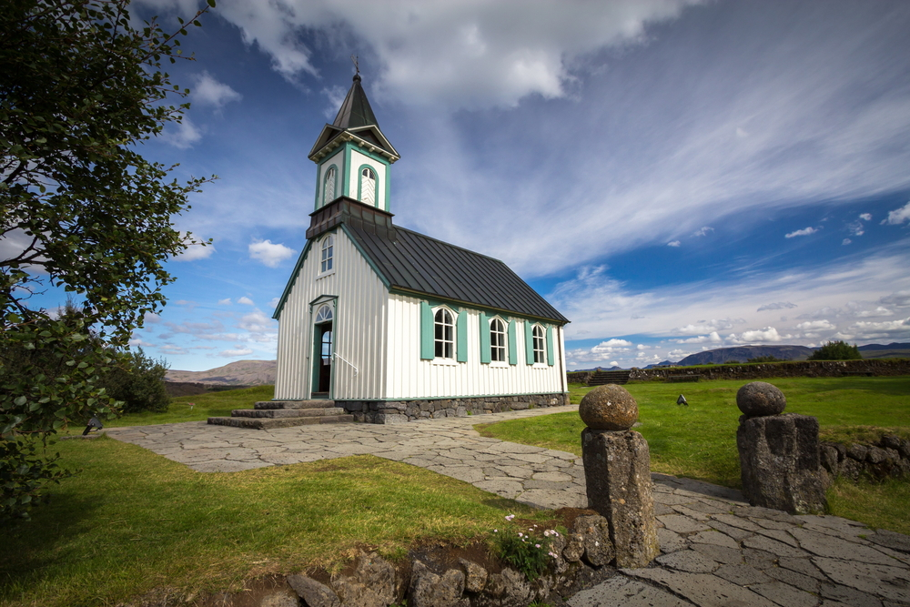 A simple yet very old church in a grassy area in Iceland's Thingvellir National Park. It is white with green trim and a black roof. There is a stone pathway that leads up to the front of it.