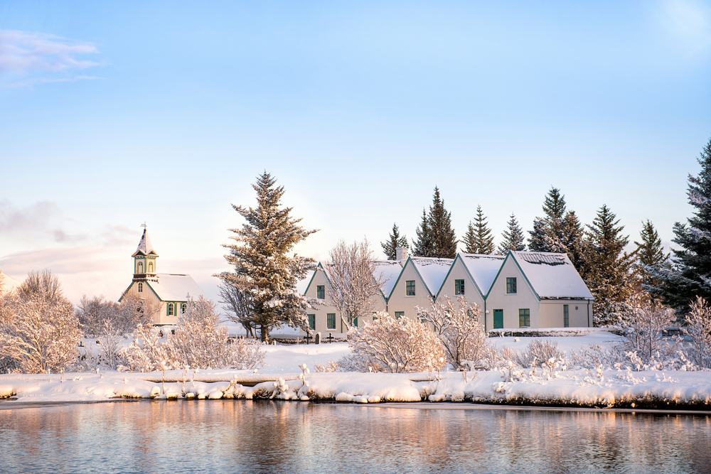 Looking across a lake in the winter at a row of homes connected and an old church. The area is covered in snow in Thingvellir National Park.