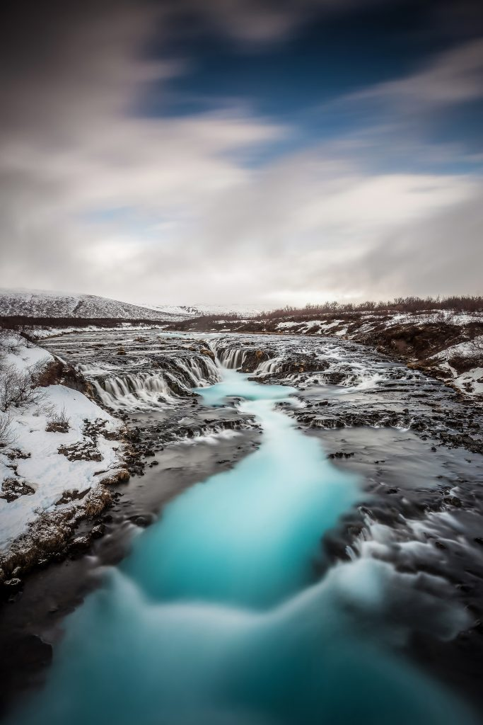 the blue water of Bruarfoss waterfall in the winter with snow surrounding it