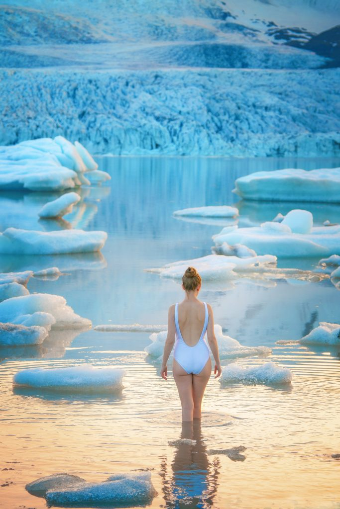 walking in the water at the Fjallsarlon Glacier Lagoon with floating icebergs and the glacier in the background