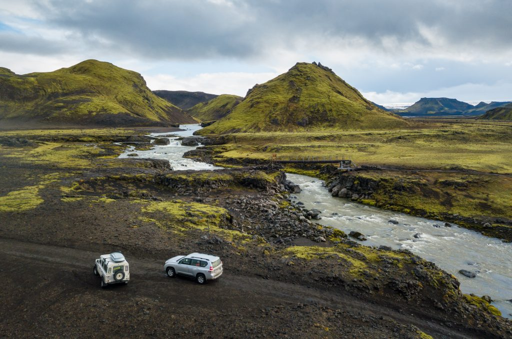 two cars having just made a river crossing in the highlands