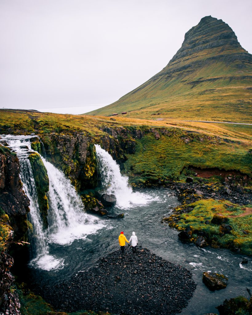 standing at the base of Kirkjufellsfoss with Kirkjufell in the background