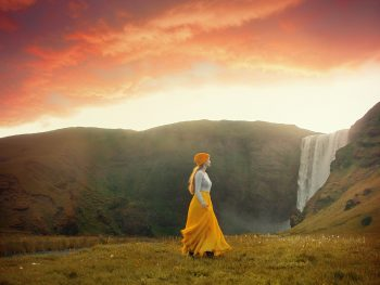 walking in front of the Skogafoss waterfall at sunset