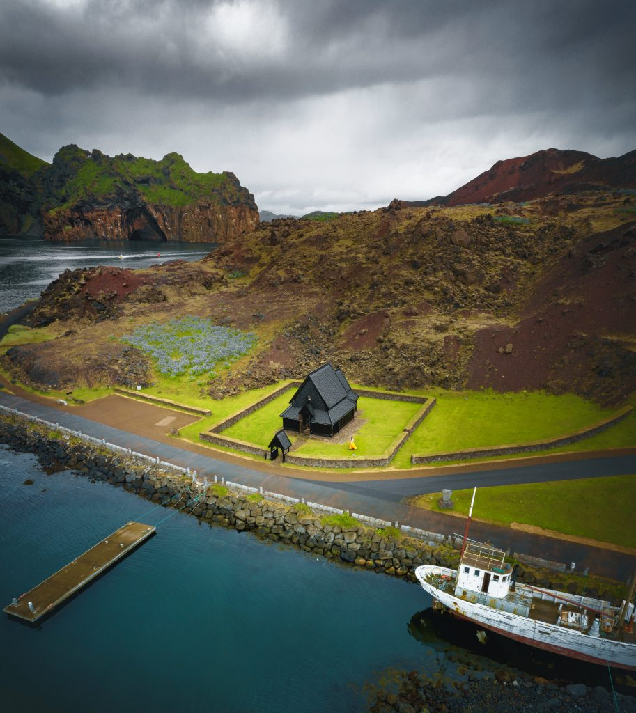 a view from above of the Heimaey Stave Church and the surrounding harbor and landscape