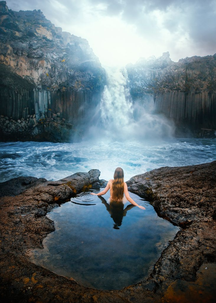 Woman sitting in a hot spring in front of Aldeyjarfoss.