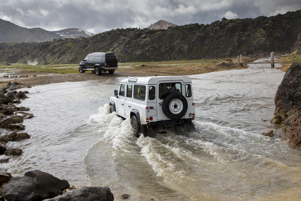 A 4x4 vehicle crossing a river in Iceland's highlands.