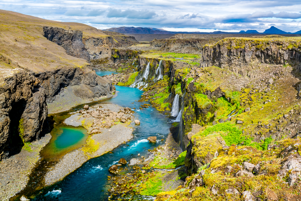 Waterfalls falling into the Sigoldugljufur canyon and a bright, blue river.