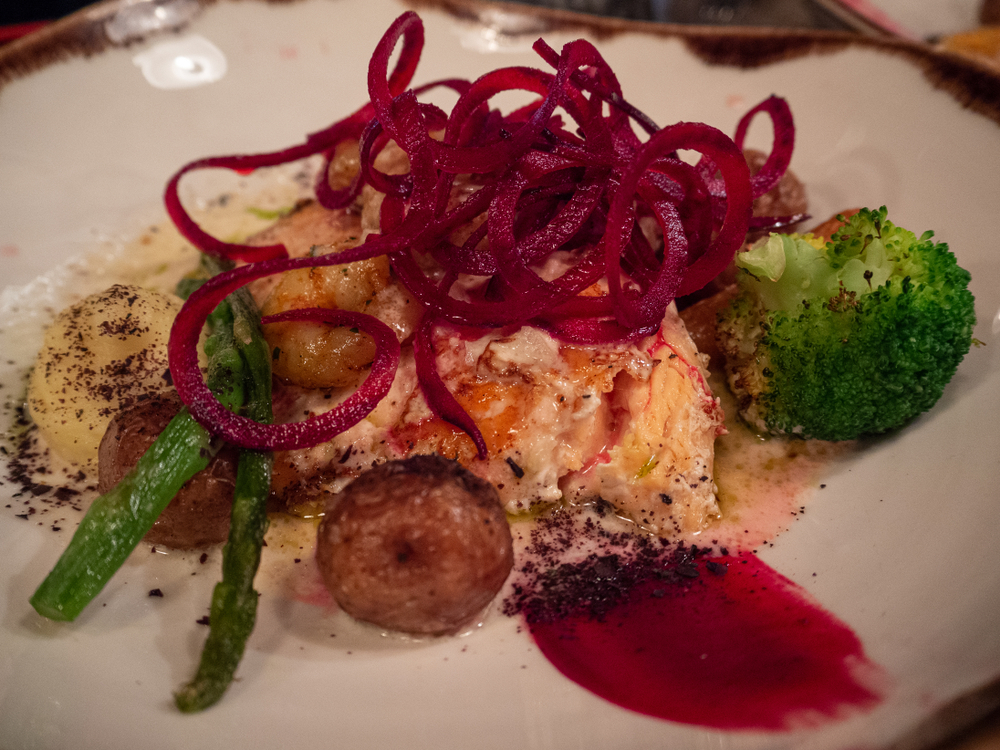 Salmon and vegetables on a plate with pickled beetroot on top