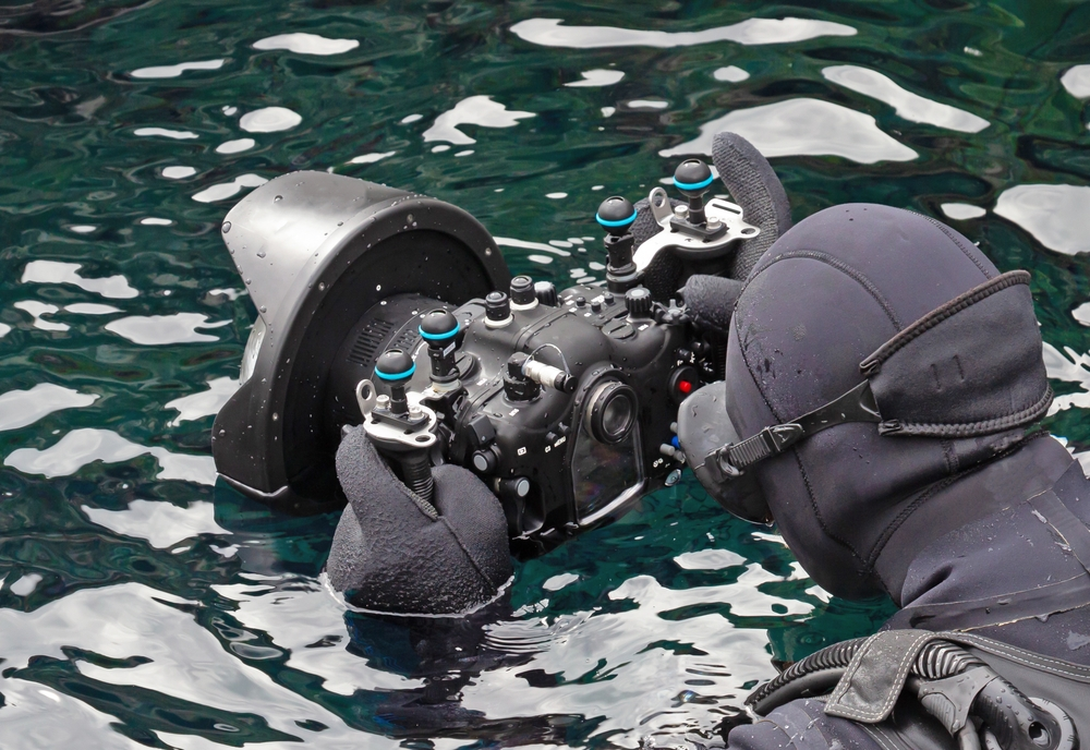 A diver with a camera, ready to take photos of other people snorkeling silfra in iceland