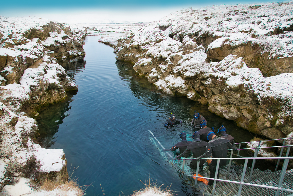 Ice and snow capped land surrounds the fissure as divers get ready for their tour at the Silfra landing.